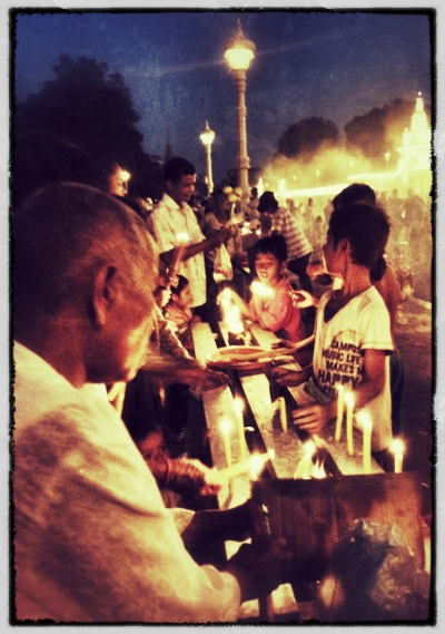 Mourners light candles (Royal Palace at night)